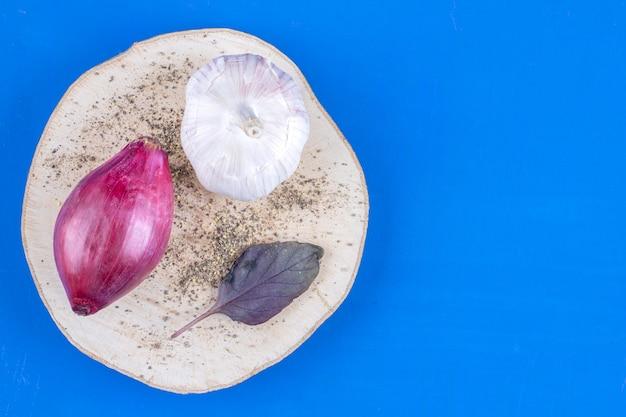 나무 조각에 신선한 익은 보라색 양파와 마늘.
