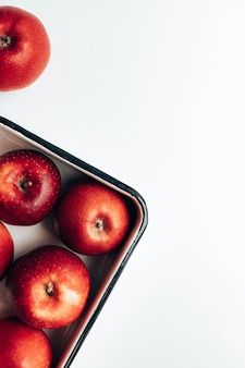 Fresh ripe red apples in enamel container and on the table flat lay top view copy space