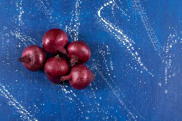 Cipolle rosse mature fresche disposte sulla superficie di marmo.