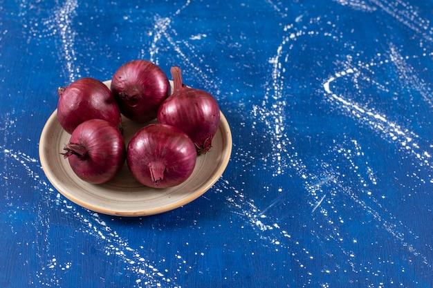 세라믹 접시에 신선한 익은 붉은 양파를 배치합니다.