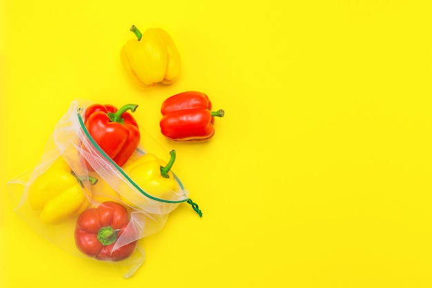 Fresh ripe red and yellow peppers in reusable eco friendly mesh bags on the yellow.
