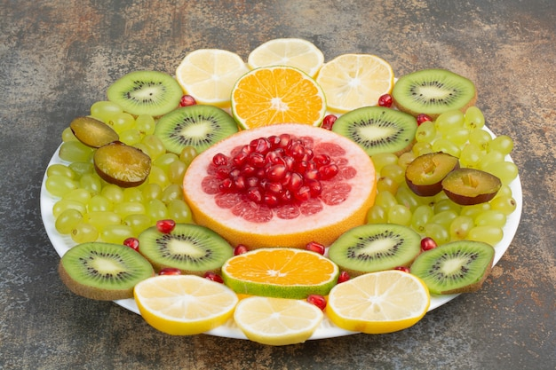 Свежие спелые ломтики фруктов на белой тарелке. фото высокого качества