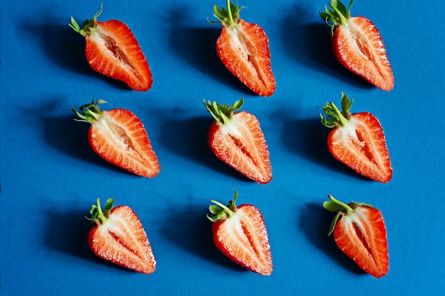 Fresh ripe strawberries on a blue background.  berries, fruit pattern, flat lay, top view, copy space.