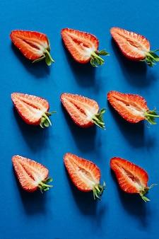 青色の背景に、新鮮な熟したイチゴ。ベリー、フルーツパターン、フラット横たわっていた、トップビュー、コピースペース。