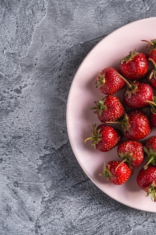 Свежие спелые плоды клубники в розовой тарелке, летние витаминные ягоды на серой каменной поверхности, вид сверху