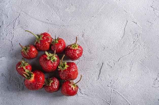 Свежие спелые плоды клубники, летние витаминные ягоды на сером каменном фоне, вид сверху копией пространства