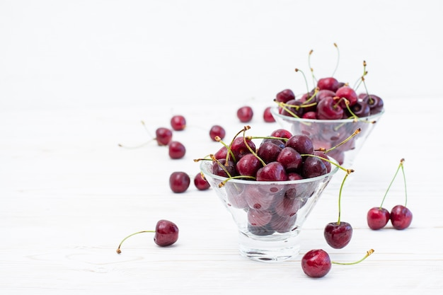 Fresh ripe sweet cherries in water drops in bowls on a white wooden table