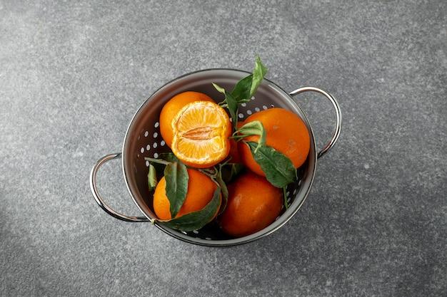 Fresh ripe tangerines in gray colander