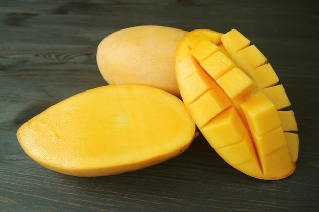 Fresh ripe thai nam dok mai mangoes whole fruit and cut in half on dark brown wood