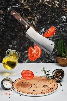 Fresh ripe tomatoes are cut with a knife and dropped onto plate with rosemary, salt, pepper and olive oil