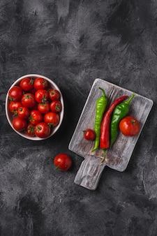 唐辛子と古い木製のまな板の近くにボウルに新鮮な完熟トマト