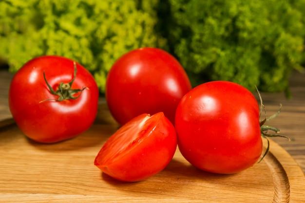 그린 샐러드와 함께 나무 테이블에 신선한 익은 토마토
