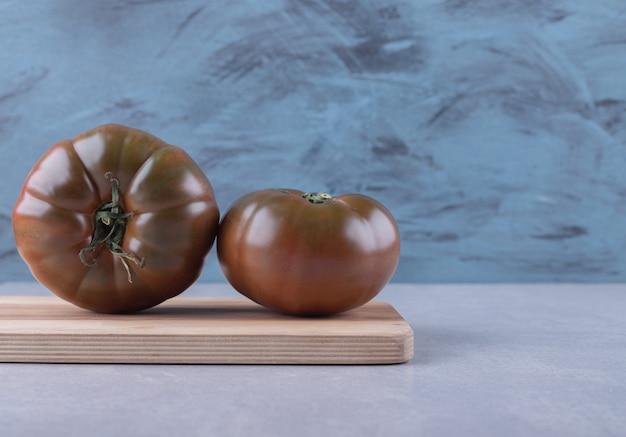 Fresh ripe tomatoes on wooden board.
