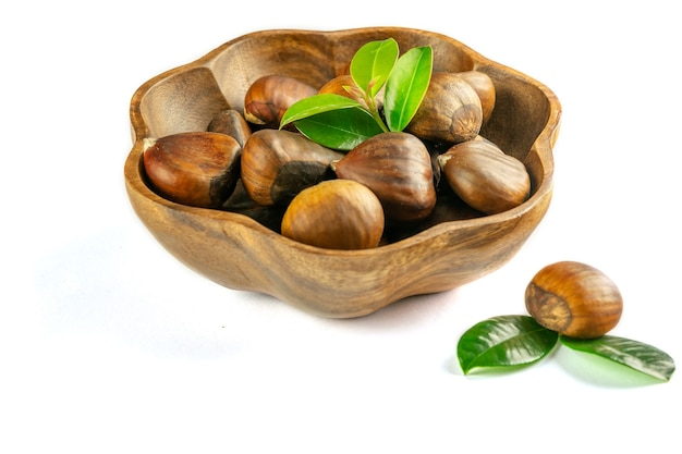 Fresh ripe unpeeled chestnuts in the wooden bowl on the white background