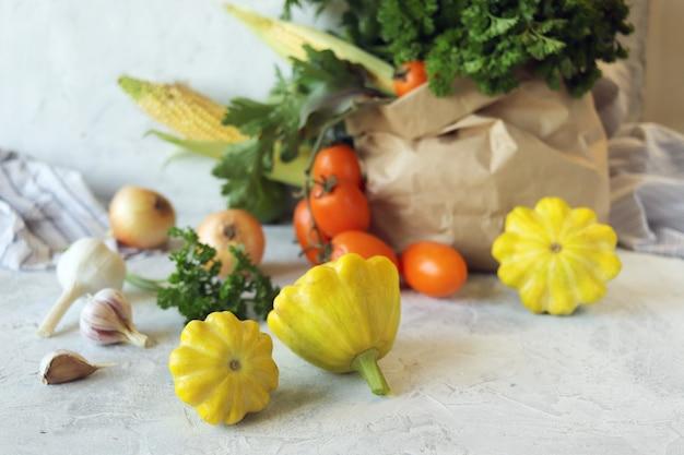 明るい背景の生態学的な紙袋に新鮮な熟した野菜や緑の品種