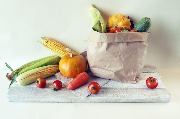 明るい背景の生態学的な紙袋に新鮮な熟した野菜の品種