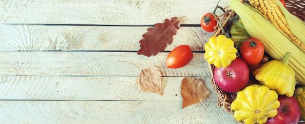 木製のテーブルの収穫の概念のバスケットに新鮮な熟した野菜や果物