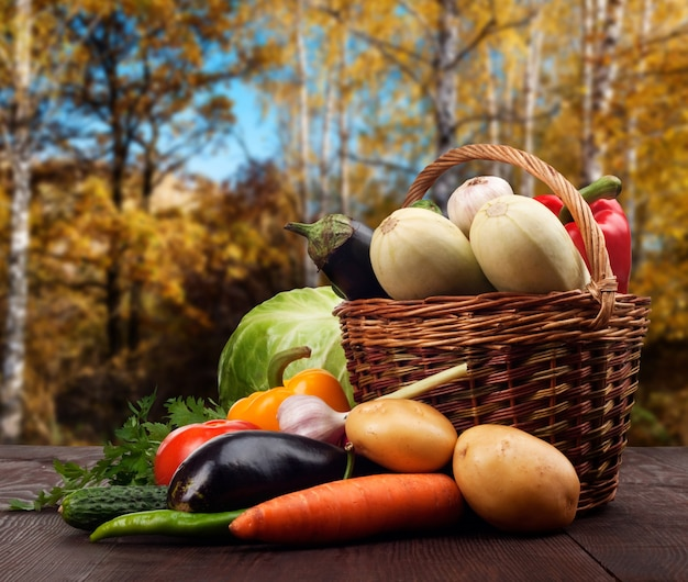 Fresh ripe vegetables in a basket on wooden table