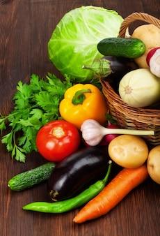Свежие спелые овощи в корзине на деревянном столе