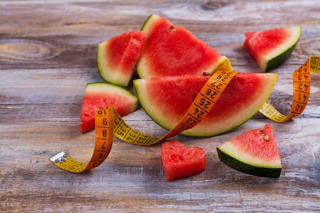 Fresh ripe watermelon slices, dumbbells and measuring tape on wooden background