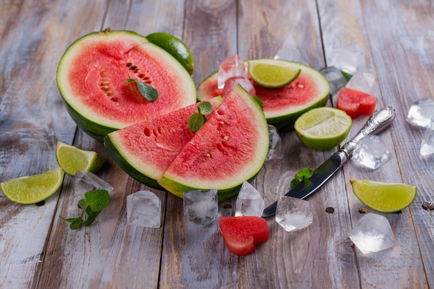 Fresh ripe watermelon slices, lime and mint on wooden table