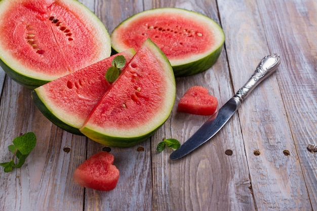 Fresh ripe watermelon slices and mint on wooden table
