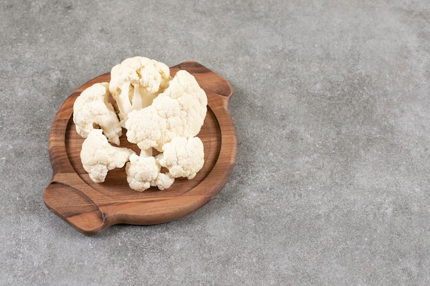 Fresh ripe white cauliflower placed on wooden board.
