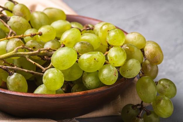 Свежие спелые белые ягоды винограда в деревянной миске на льняной скатерти