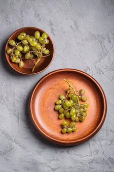 木のプレートと石のボウルに新鮮な熟した白いブドウの果実