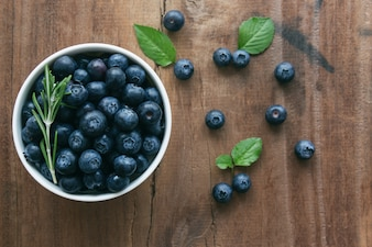 Fresh ripe wild blueberries in white bowl on rustic wood table.