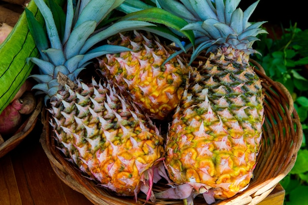 Fresh ripe yellow and green pineapples in a wicker basket at the market