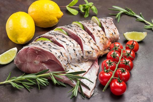 金属製のトレイに新鮮な川の魚。チェリートマトとローズマリーのレモンと小枝。