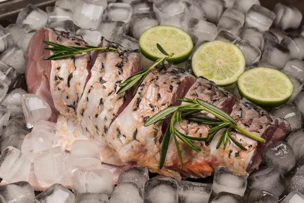 氷の上で新鮮な川の魚。ローズマリーとレモンの小枝。