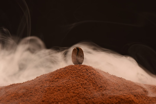 Fresh roasted coffee bean stands on a scattering of ground coffee in the smoke