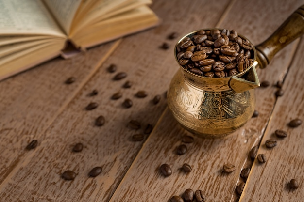 Fresh roasted coffee beans in cezve opened book and cup on wooden table.