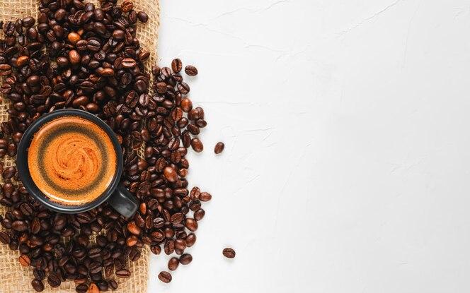 Chicchi di caffè tostati freschi e una tazza di caffè espresso caldo con schiuma, posizionata a sinistra su un'ampia superficie bianca di cemento