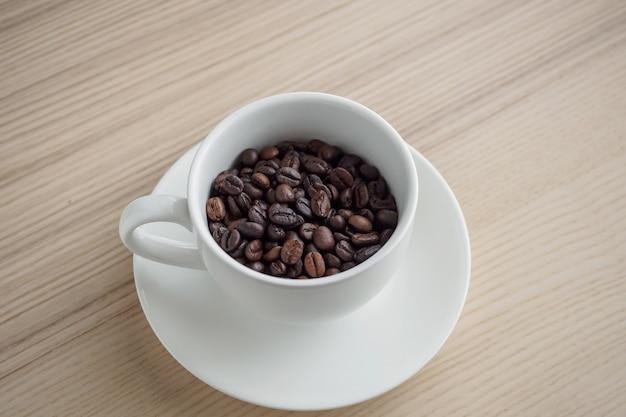 나무 테이블에 흰색 컵에 신선한 볶은 커피 콩