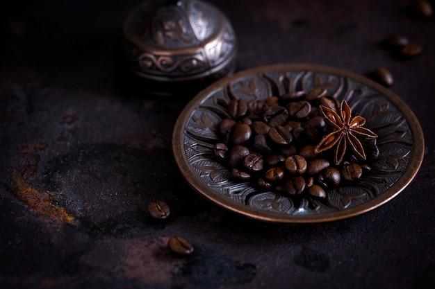 Свежий жареный кофе в зернах на красивой тарелке