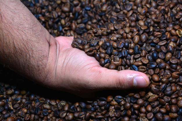 カップ状の手から黄麻布の袋に注ぐ新鮮な焙煎コーヒー豆