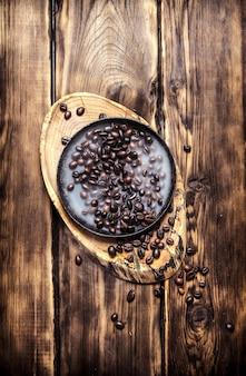 냄비에 신선한 볶은 커피. 나무 배경.