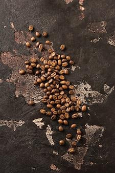 Свежие обжаренные цельные зерна кофе арабика, разбросанные по старой коричневой текстурированной поверхности