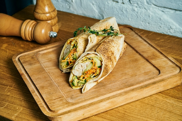 Fresh roll in pita bread with chicken kebab, sauce and vegetables on a wooden board. street food. shaurma or shawerma
