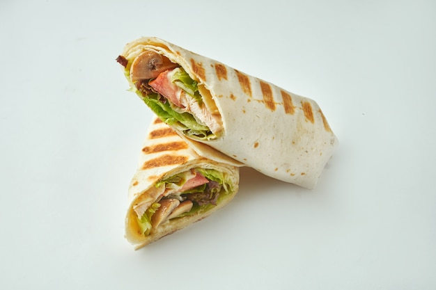 Fresh roll with chicken, tomatoes, cheese and lettuce in pita bread on a white table. baked chicken shawarma