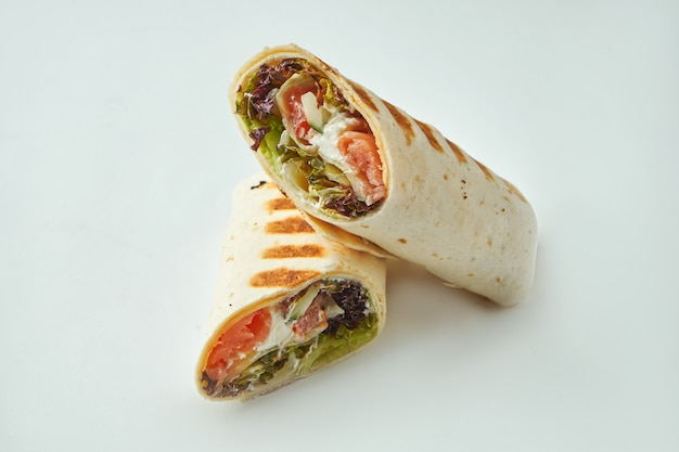 Fresh roll with salmon, cream cheese, cucumber and lettuce in pita bread on a white table. seafood shawarma