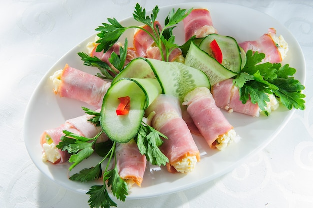 Fresh rolled ham on white plate.