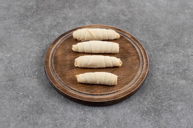 Biscotti fatti in casa arrotolati freschi su tavola di legno.