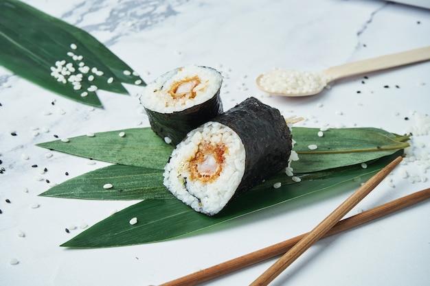 Свежие рулетики с жареными темпура креветками, рисом и норм на белом. японские традиционные суши роллы.