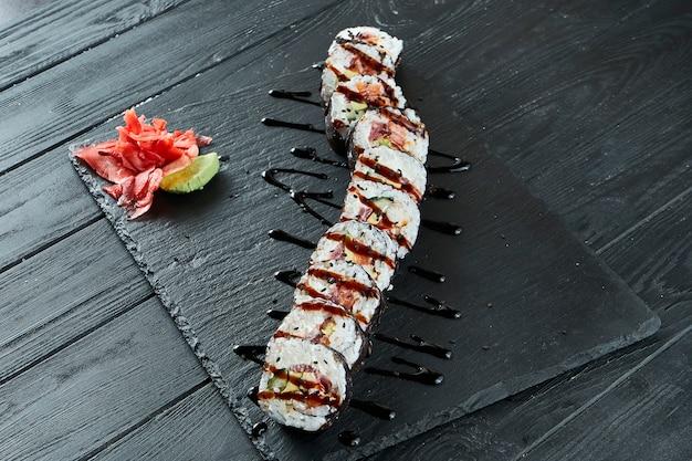 나무 표면에 검은 접시에 연어, 캐 비어, 오이, 필라델피아 치즈와 신선한 롤. 일본 스시 롤