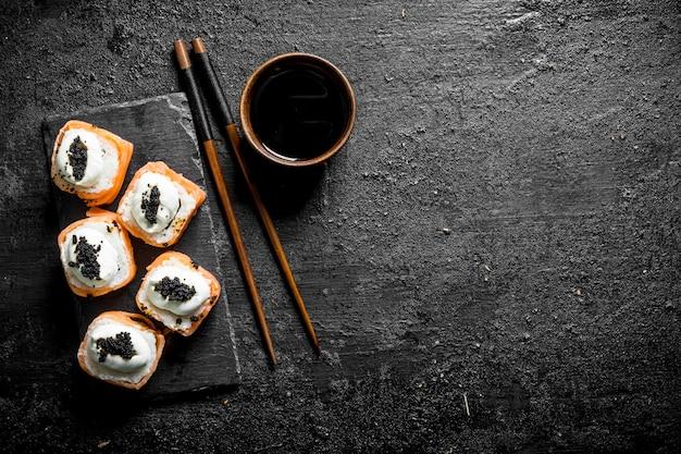 Свежие роллы с лососем, сливочным сыром и икрой. на черном деревенском фоне
