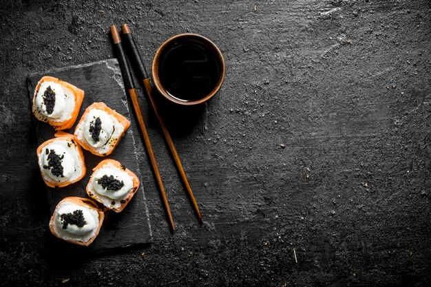 Fresh rolls with salmon, cream cheese and caviar. on black rustic background